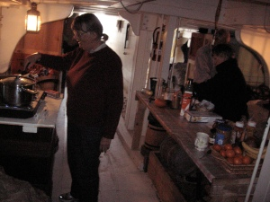 Barbara Batdorf at the stove, with Kathleen Carney laying out breakfast on the table