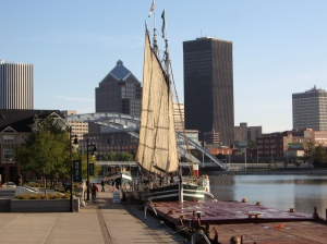 Sails set on the Lois McClure, with Rochester in the background