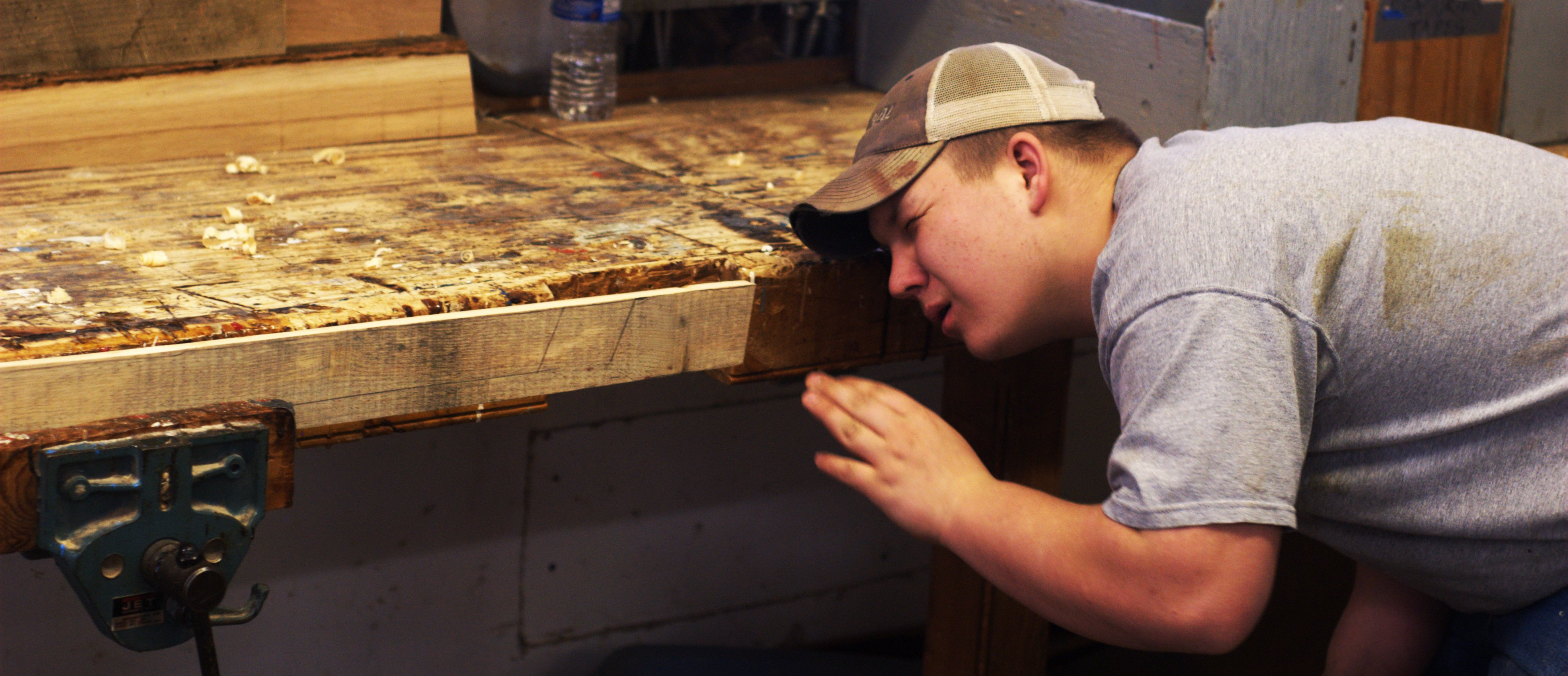 Nick ____ checking the edge of a plank for smoothness