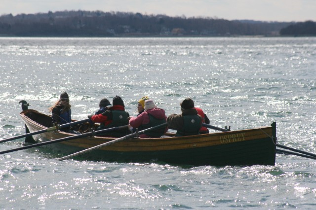 "With coxswain Emily Weber of Ferrisburgh steering, the Vergennes rowing team drives towards the finish line at the ""Snow Row "" 2011"