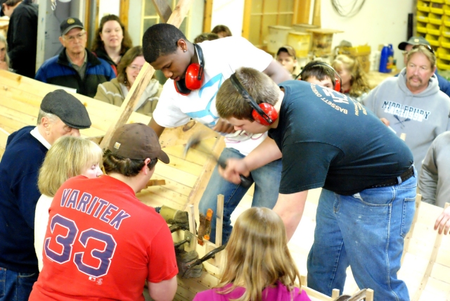 Students perform the final steps of installing a rib in front of their families