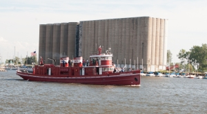 The EDWARD M COTTER, the oldest working fireboat in the United States (built 1900) passing in front of the grain silos on the Buffalo River (photo: Tom Larsen)