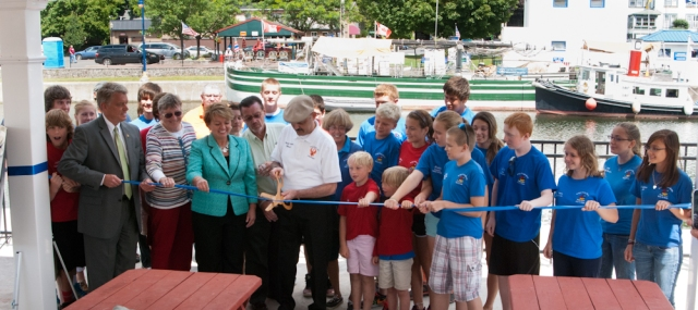 Mayor Tony Fratto, Canal Corps Director Brian Stratton, Senator Pattie Richie and the Bridgehouse Brats cutting the ribbon to open a new pavilion on the Phoenix waterfront (photo: Tom Larsen)